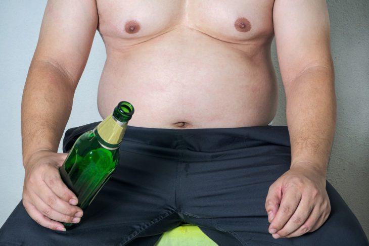 w ręce piwo a w tle brzuszek piwny